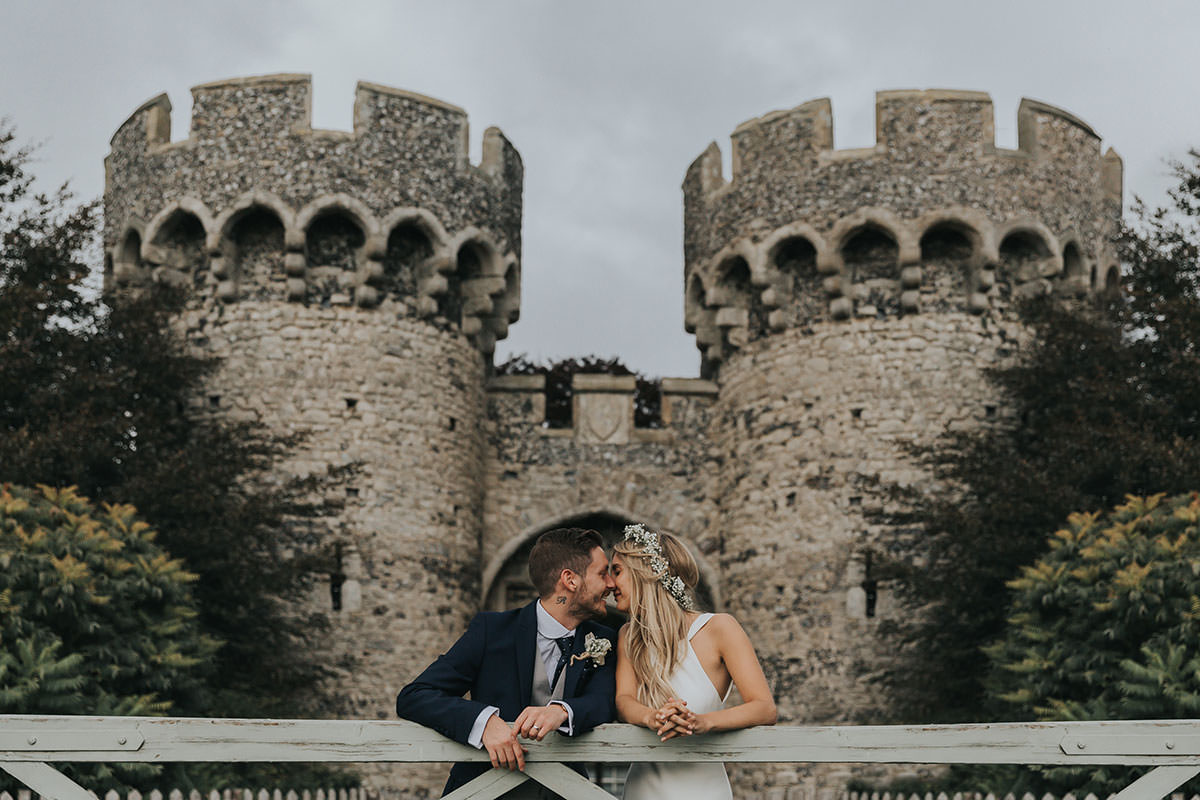 bride and groom pose at cooling castle wedding