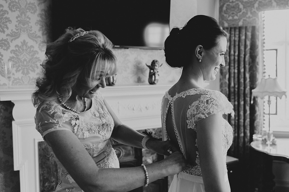 crondon park wedding mother helping bride with dress