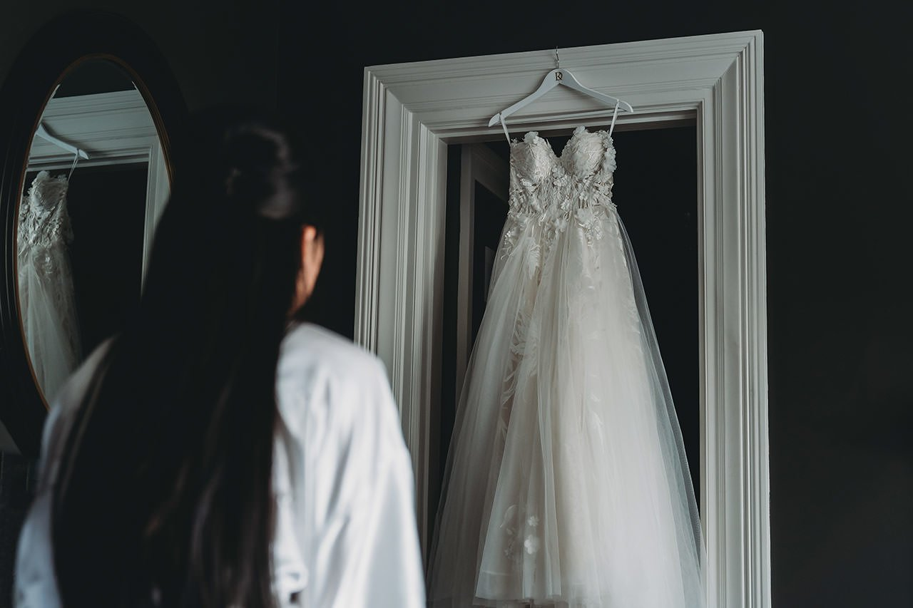 bride looking at Riki Dalal wedding dress at Swynford Manor